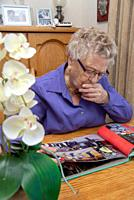 old woman looking at photoalbum.