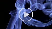 Thin trickle of bright neon blue smoke slowly rising graceful twists up on black background. Colored smoke blowing from bottom to top. Closeup