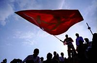 NEPAL Kathmandu -- 28 Apr 2006 -- A supporter of the seven-party alliance flies a large party flag at a rally in Ratna Park in central Kathmandu. Desp...
