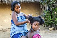 Young girls, friends arranging their hair, small town in the Tsingy de Bemaraha National Park. Madagascar, Africa.