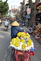 Vietnamese woman selling lemons from the back of her motorcycle, Hanoi city centre, Vietnam, Asia
