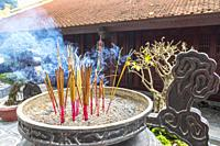 Burning joss sticks for prayer at the Tran Quoc pagoda at Westlake, Hanoi, Vietnam, Asia.
