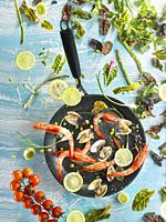Composition with vegetables and seafood, flying over a frying pan, with blue background.