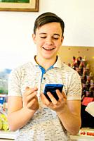 teen boy looks at the smartphone in his home- portrait of boy reading on the smartphone.