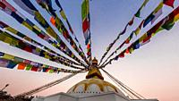Prayer flags ring the massive stupa of the Boudhanath Temple. It is the largest stupa in Nepal and the holiest Tibetan Buddhist temple outside Tibet. ...