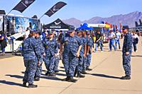 Sailors of the USCG in camouflage blue uniforms undergoing a drill exercise at the Davis-Monthan AFB airshow day in Tucson AZ.