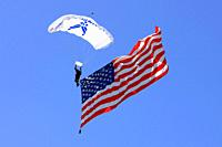 Member of the USAF Parachute team showly comes to earth with a giant American flag attached to his ankle at the Tucson Airshow AZ.