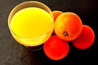 Orange juice with oranges on grey background
