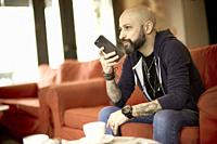 man in cafe using smartphone, Paris, France