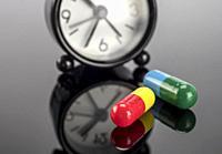 pills next to a clock, conceptual image.