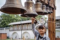 Girl ringing the bells of Andronikov monastery in Moscow.