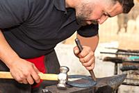 Blacksmith working on the anvil, making a horseshoe .