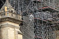 PARIS, FRANCE - 19 APRIL 2019 Notre Dame cathedral, a man positions sandbags along the edge of the walls. The remains of the melted scaffolding behind...