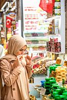 Beautiful Muslim woman in headscarf and fashionable modern clothes smells traditional soaps made from natural herbs and sold in Egypt Bazaar,Eminonu,I...