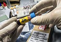Police expert gets blood sample from glass bottle in Criminalistic Lab, conceptual image.