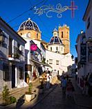 Typical street with Iglesia de la Virgen del Consuelo on background. Altea. Alicante. Valencian Community, Spain.