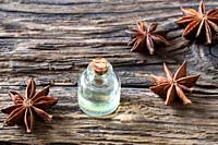A bottle of essential oil with star anise on a rustic background.