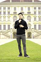 young man in front of aristocratic Nymphenburg Palace, in Munich, Germany.