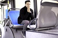 young man with folded hands sitting in bus, in Munich, Germany.
