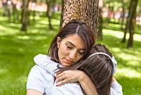 Young mom hugs daughter showing love and support, caring young mother embrace girl. Happy mother hugging her daughter with love and natural emotion sm...
