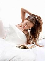 Woman in bed reading a book.
