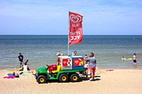 John Deere Gator transformed into ice cream truck selling ice creams to tourists on the beach at seaside resort along the North Sea coast