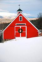 A red barn is decorated with a Christmas wreath in the highlands of New England.