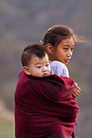 KHONOMA VILLAGE, NAGALAND, INDIA, December 2016, Young Naga girl carryies sibling on her back.