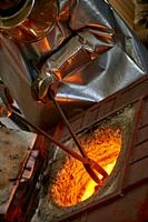 The artist is melting the bronze before filling the casting mold with with the hot metal.