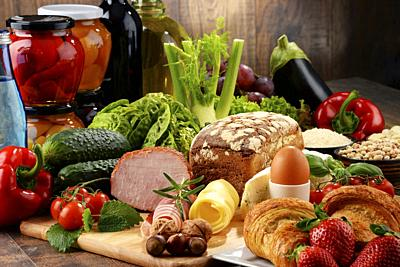 Composition with variety of organic food products on kitchen table.