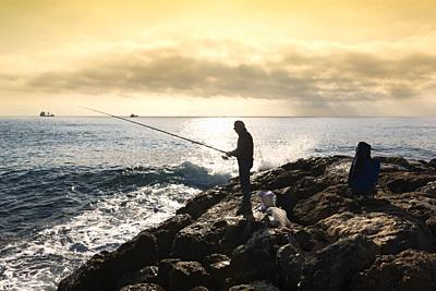 Savona, Italy. A fisherman standing with the fishing rod in his hand, he is on the rocks at sunset, near him buckets and equipment in bags, on the bot...
