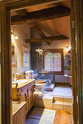 Main bathroom with toilet and clawfoot bathtub on raised ceramic tile platform on the upper floor inside an old circa 1850 Canadiana cottage style hom...