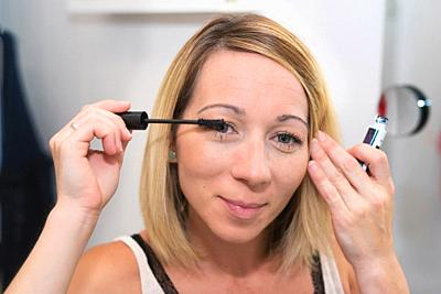 Beautiful blonde woman applying mascara on her eyelashes.