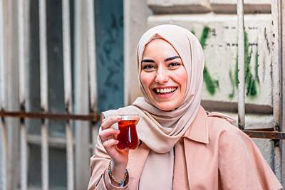 Beautiful Muslim woman in headscarf and fashionable modern clothes drinks Traditional Turkish drinks tea. Modern Muslim women lifestyle or travel tour...