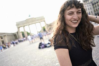 smiling woman next to Brandenburg Gate in Berlin, Germany