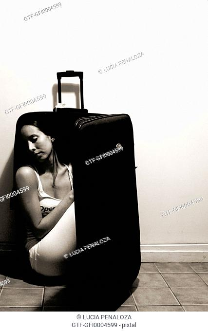 Young woman in a suitcase