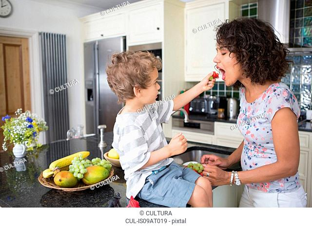 Mother and son in kitchen, sharing fruit