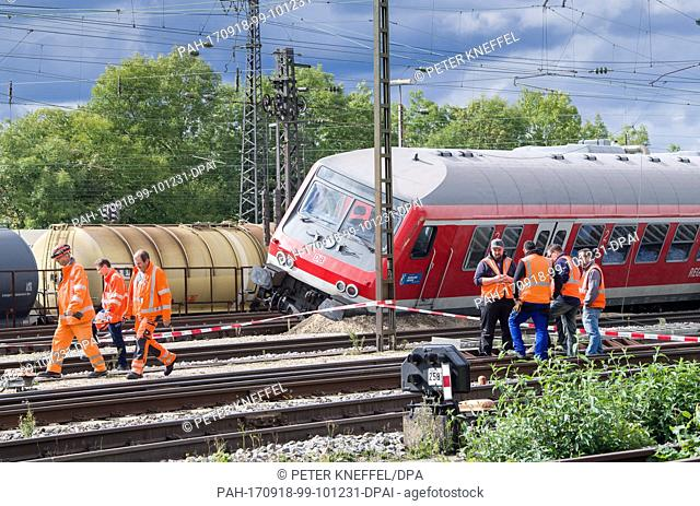 Railway workers standing near a passenger train which was involved in an accident in Augsburg, Germany, 18 September 2017
