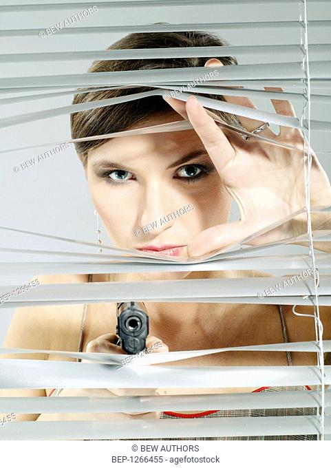 Woman's portrait taking a shoot out of the blinds