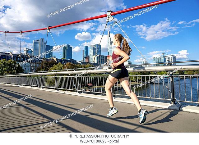 Germany, Frankfurt, young woman running on bridge