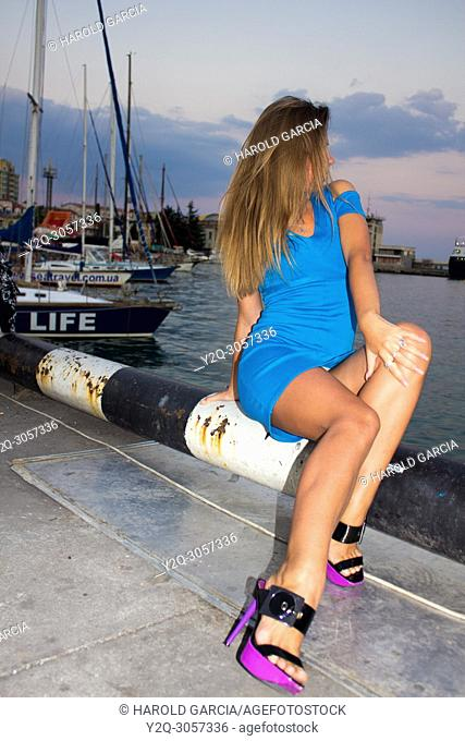 Beautiful seated woman in the shore of the port in Yalta, Crimea