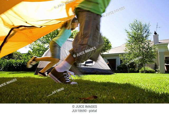 Kids running with tent in backyard