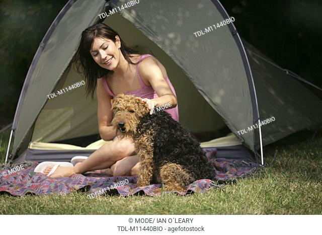 A dark haired girl sitting infront of a tent with her dog