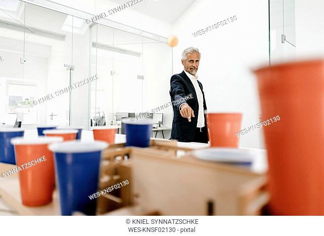 Mature businessman with architectural model in office throwing a ball