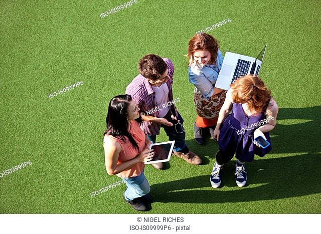 Four people standing on asto turf with technological equipment