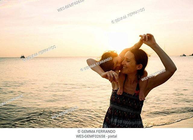 Thailand, Koh Lanta, happy mother with baby girl on her shoulders at seashore during sunset