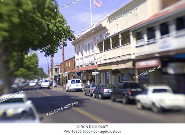 Hawaii, Maui, Lahaina, storefronts of Front Street on bright day, blurred car and people
