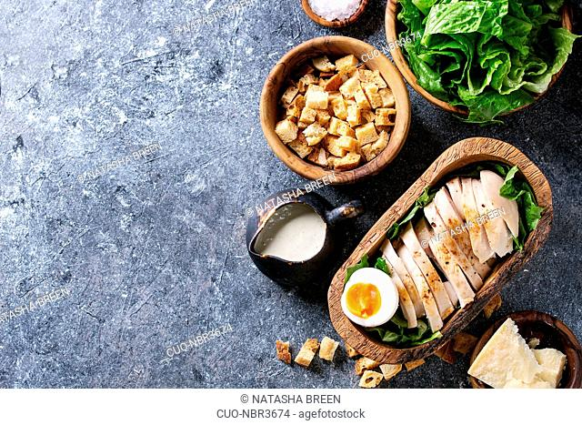 Bowls of ingredients for cooking classic Caesar salad. Sliced baked chicken breast, green roman salad, parmesan cheese, egg, croutons, salt