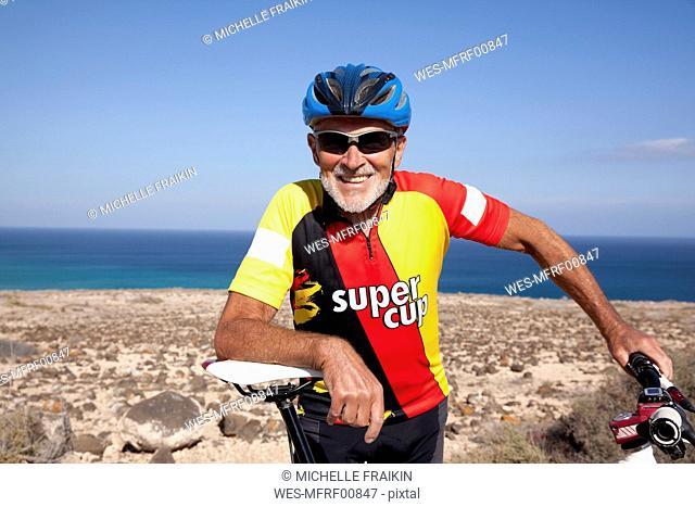 Spain, Canary Islands, Fuerteventura, smiling senior man with mountainbike