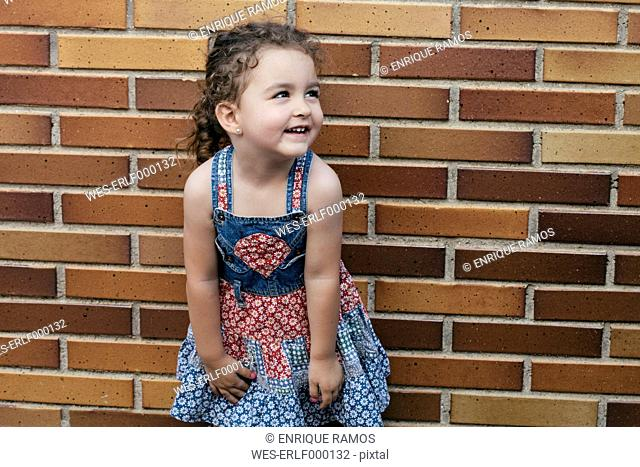 Portrait of smiling little girl wearing patterned summer dress